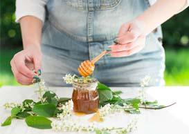Woman outdoors mixing honey