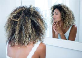Woman looking in mirror at eczema symptoms
