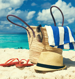 Beach bag and towel on tropical beach