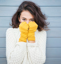 Young woman in sweater and gloves