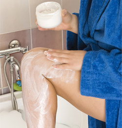 woman applying body lotion to her leg