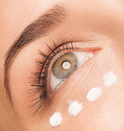 Close up of a woman's eye with dots of eye cream under it