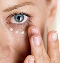 woman applying eye cream to her face