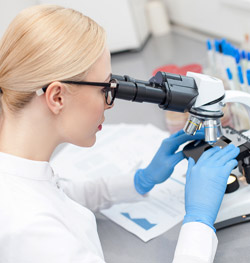 Female scientist looks at human growth factors through microscope