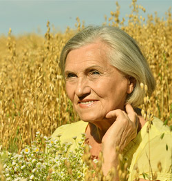 A natural-looking woman standing in a field