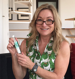 marta holding a bottle of Clairty RX get fit healthy skin serum