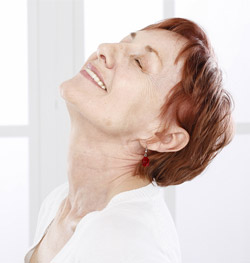 smiling senior woman throws head back